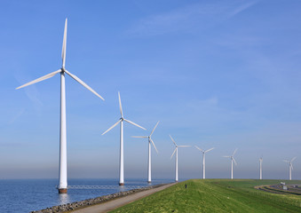 Modern windmills near the shore along a green grassy dike