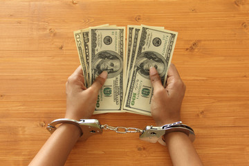 Person with handcuffs holding dollar bills
