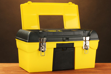 Open yellow tool box on brown background close-up