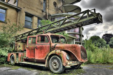Vintage abandoned firetruck in front of a derelict building
