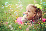 Fototapety Happy little girl playing with bubbles
