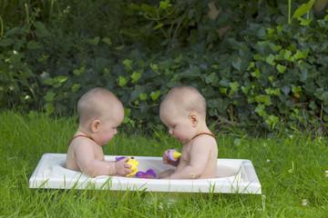 identical twin sister having a bath in the garden