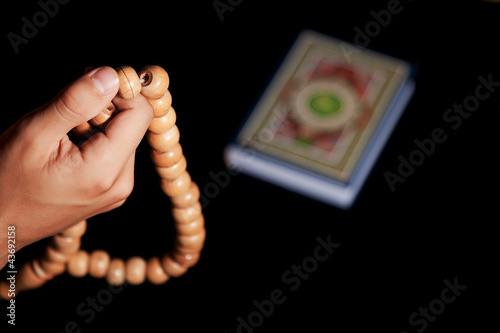 hand of young man with rosary on black background