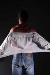 spogliarello uomo in jeans e camicia bianca