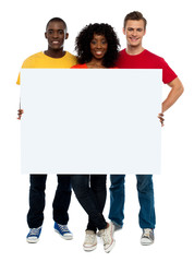 Smiling teenagers presenting blank billboard
