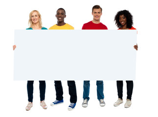 Confident young group showing blank poster