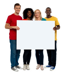 Team of young people holding whiteboard