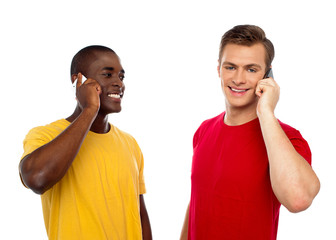 Two handsome men communicating on cellphone