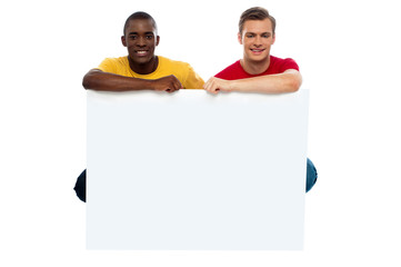 Casual young guys posing with blank billboard