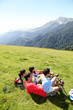 Family laying down the grass enjoying mountain view