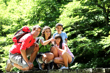 Family on a bridge in mountain observing nature