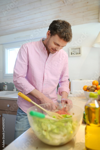 Man at home preparing salad for dinner
