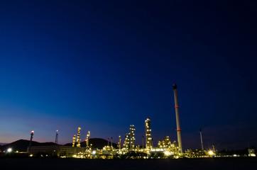 Petrochemical industry on sunset dark blue sky.