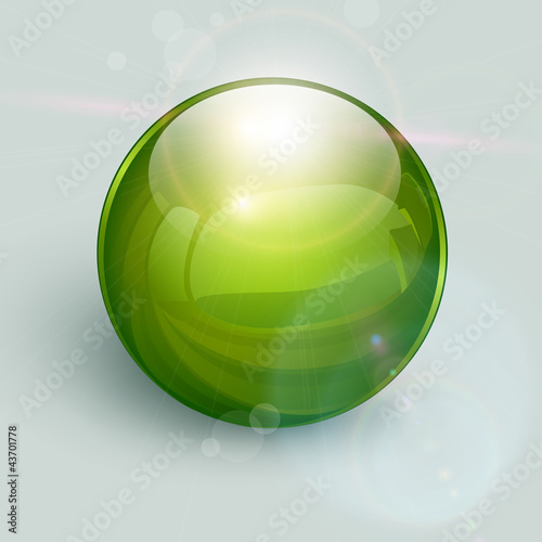 Green glass ball on background with lens flares