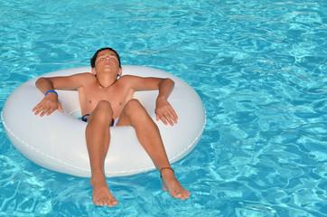 Adolescent qui se repose dans une piscine