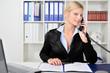 Junge blonde Geschäftsfrau telefoniert im Büro