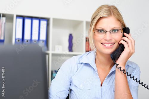 Junge blonde Mitarbeiterin telefoniert im Büro