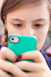 Extreme close-up of girl texting mobile cell phone