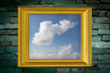 cloud picture and golden frame on old brick wall