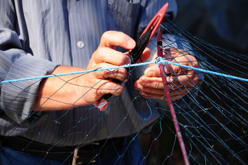 hands repairing fishing net