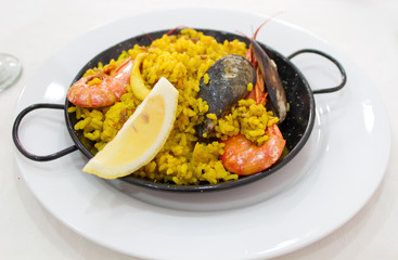 Portion of paella served in metal plate