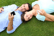 Couple relaxing in grass while using smartphone