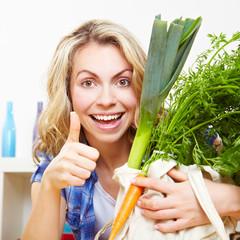 Frau mit Gemüse hält Daumen hoch