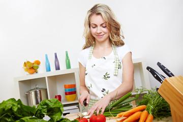 Frau schneidet Gemüse in Küche