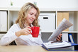 Frau im Büro liest Zeitung