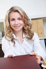 Frau überreicht Bewerbungsunterlagen