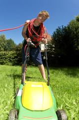 Teenager beim Rasenmähen