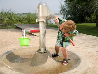Kleiner Junge am Brunnen