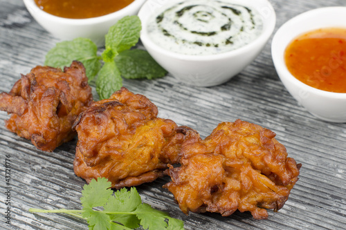 Onion Bhajis, mango chutney, mint raita & chili sauce on a slate