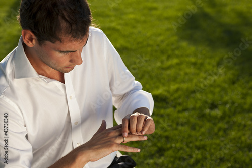 Young man looking at his wedding ring