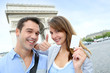 Cheerful couple holding tourist ticket by the Arch of Triumph