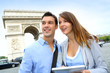 Couple using tablet by the Arch of Triumph