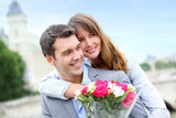 Fototapety Portrait of romantic man giving flowers to woman