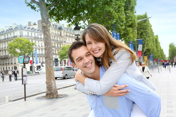 Man giving piggyback ride to girlfriend on the Champs Elysees