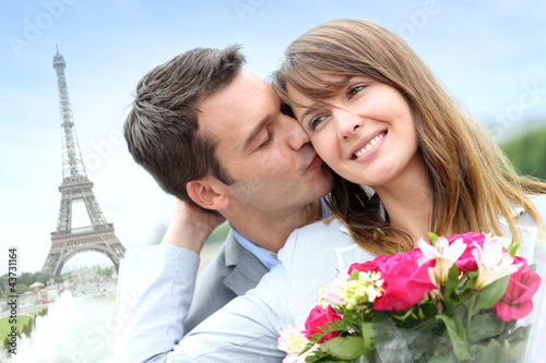 Man giving flowers to woman in Paris by the Eiffel Tower