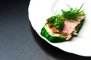 Closeup of ham, cucumber and parsley canapes