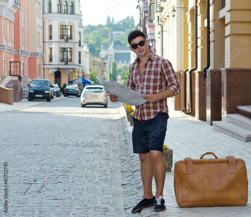 Male tourist with a suitcase and map