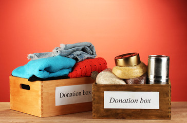 Donation boxes with clothing and food on red background