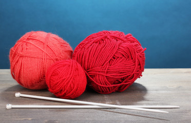 Red knittings yarns on wooden table on blue background