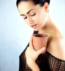 Oryginalna kobieta w bluzce trzymająca w dłoni kubek z herbatą
