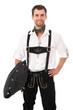Junger Mann in bayerischer Tracht mit Strickjacke unterm Arm