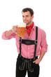 Junger Mann in Lederhose trinkt ein Maß Bier