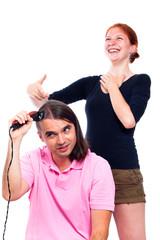 Man shaving his hair and woman laughing at him