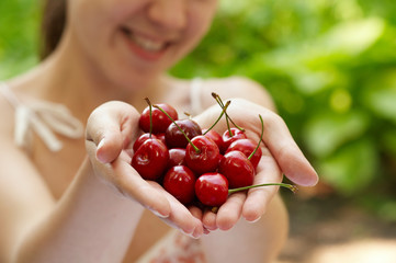 she holds a handful of  red cherries