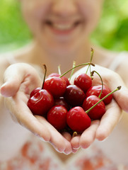 Smiling girl holding a handful of red cherries