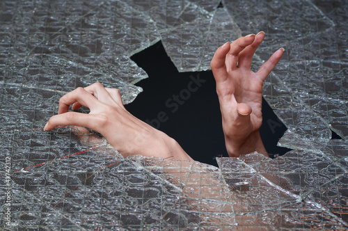 Two hands make their way through the broken glass